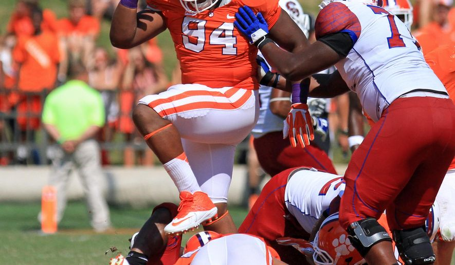 In this Sept. 7, 2013, photo, Clemson defensive lineman Carlos Watkins (94) leaps over the pile during an NCAA college football game against S.C. State at Memorial Stadium in Clemson, S.C. Watkins simply wanted to spend time with hometown friends the weekend after his team's victory at North Carolina State. But traveling to a cookout, the car Watkins was riding in hit an electrical pole killing one of his closest friends and injuring Clemson's rising defender. (AP Photo/Anderson Independent-Mail, Mark Crammer) GREENVILLE NEWS OUT, SENECA NEWS OUT
