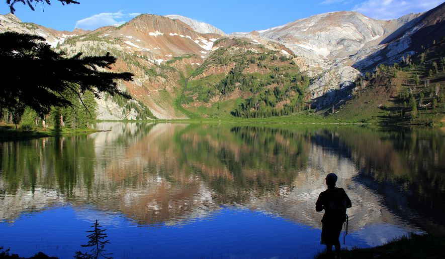 """ADVANCE FOR THE WEEKEND OF AUG. 23-24 AND THEREAFTER - In a July 31, 2014 photo, Andy Gonerka stands in front of Ice Lake in the Eagle Cap Wilderness of northeastern Oregon's Wallowa Mountains. Home to 17 mountains that eclipse 9,000 feet and derived from the Nez Perce word for """"land of running waters,"""" the Wallowas of northeastern Oregon offer what many consider the state's best backpacking experience. (AP Photo/The Statesman Journal, Zach Urness)"""