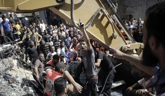 A Palestinian man chants angry slogans as rescue workers search for victims under the rubble of a house destroyed in Israeli strikes in the Rafah refugee camp, Southern Gaza Strip, Thursday, Aug. 21, 2014. (AP Photo/Khalil Hamra)