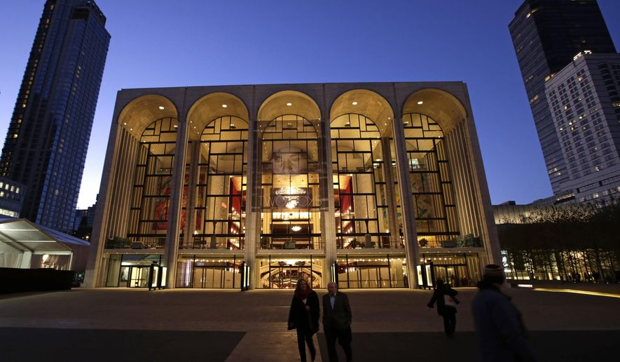 FILE- In this  Nov. 13, 2013 file photo, pedestrians stroll at dusk in front of the Metropolitan Opera House in New York's Lincoln Center. The Met and the International Alliance of Theatrical Stage Employees said Thursday, Aug. 21, 2014 they reached labor agreements with the remaining unions that had expired contract agreements. (AP Photo/Kathy Willens, File)