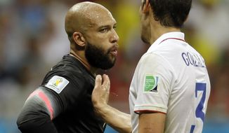 United States' Omar Gonzalez, right, pats goalkeeper Tim Howard on the chest during the World Cup round of 16 soccer match between Belgium and the USA at the Arena Fonte Nova in Salvador, Brazil, Tuesday, July 1, 2014. (AP Photo/Natacha Pisarenko)