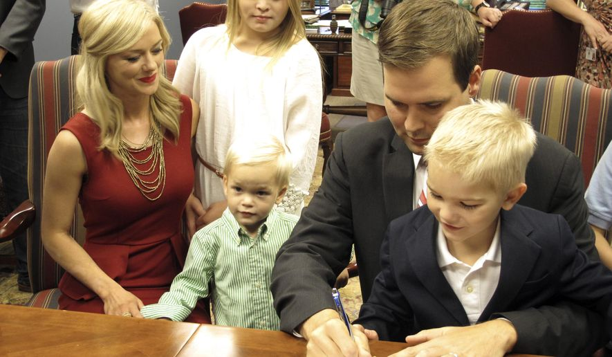 """Republican Zach Dasher, a relative of TV's """"Duck Dynasty"""" family, signs paperwork qualifying him to run for the 5th District congressional seat on Thursday, Aug. 21, 2014, in Baton Rouge, La. Dasher is one of several candidates seeking to oust U.S. Rep. Vance McAllister. (AP Photo/Melinda Deslatte)"""