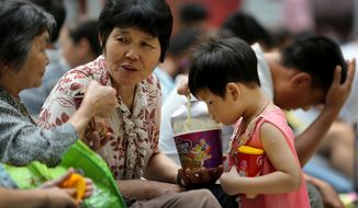 A child eats instant noodle at a train station in Beijing, Aug. 17, 2014. (Associated Press) ** FILE **