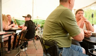 Don Amos and his wife Beth of Leesburg, Va. eat dinner with his gun at The Cajun Experience during Second Amendment Wednesdays where patrons are allowed to open carry their guns, Leesburg, Va., Wednesday, August 20, 2014. (Andrew Harnik/The Washington Times)