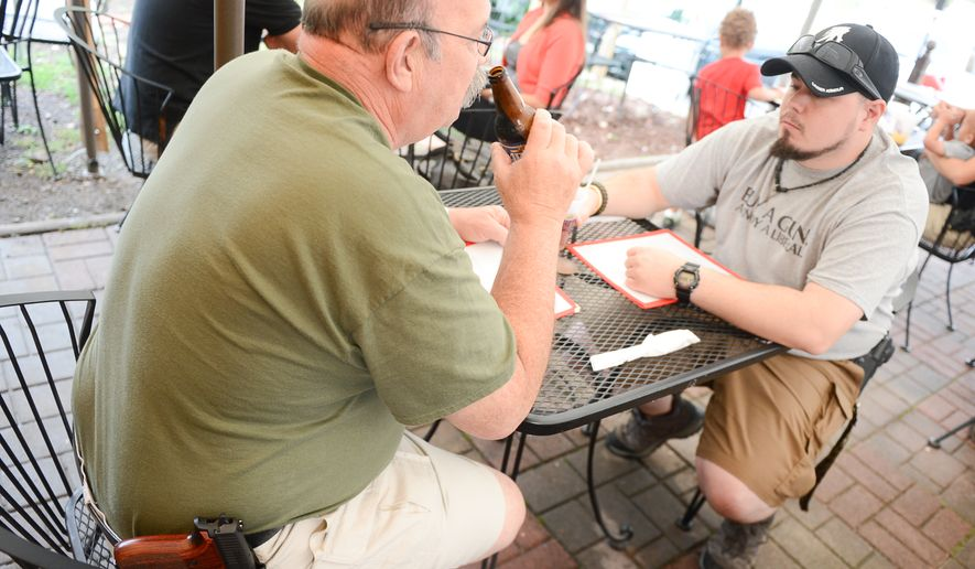 Dan Arnold and his father Pete, left, eat dinner with their guns at The Cajun Experience during Second Amendment Wednesdays where patrons are allowed to open carry their guns, Leesburg, Va., Wednesday, August 20, 2014. (Andrew Harnik/The Washington Times)