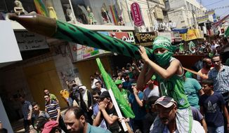 A Palestinian boy holds a representation of a rocket as supporters of Hamas chant slogans against the Israeli military action in Gaza, during a demonstration in the West Bank city of Jenin on Friday, Aug. 22, 2014. (AP Photo/Mohammed Ballas)