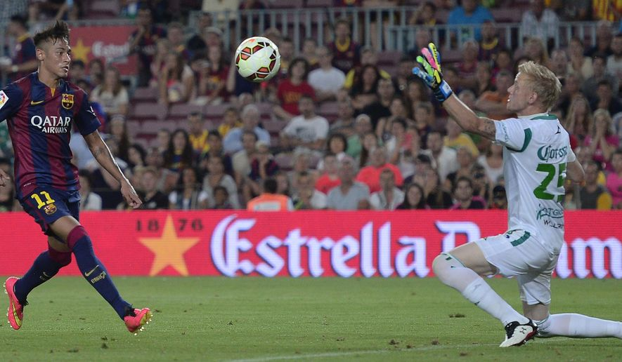 Barcelona's Neymar, from Brazil, left, scores against Leon's goalkeeper Wiliam Yarbrough during the Joan Gamper trophy friendly soccer match at the Camp Nou in Barcelona, Spain, Monday, Aug. 18, 2014. (AP Photo/Manu Fernandez)
