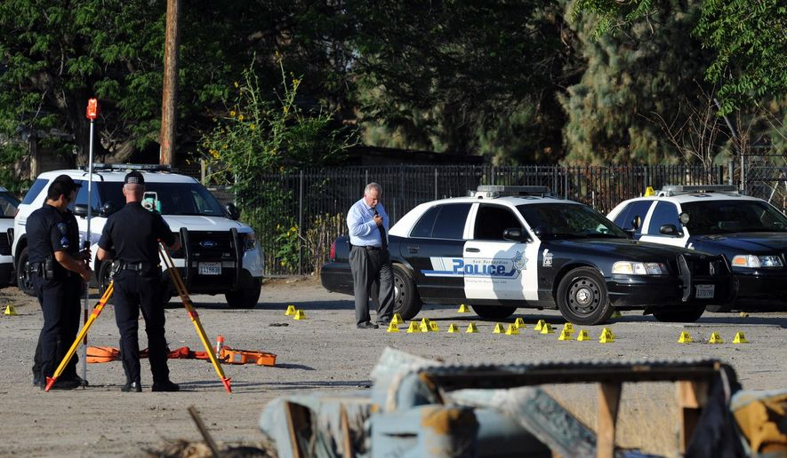 San Bernardino Police investigate the scene where a police officer shot and killed a gunman during an early morning shootout that began after another officer was gravely wounded, Friday, Aug. 22, 2014, in San Bernardino, Calif. (AP Photo/The Sun, Micah Escamilla) MANDATORY CREDIT