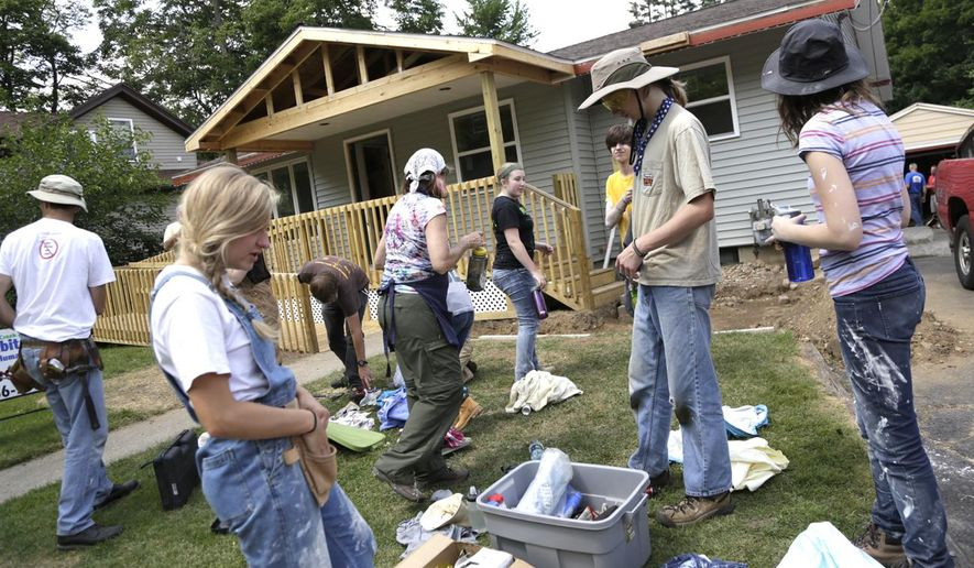 Members of Habitat for Humanity and the First Unitarian Society of Milwaukee clean up after helping refurbish a house in Albion, Mich. on Wednesday, July 30, 2014. The members were helping Stephanie Miller with her new home. (AP Photo/Jackson Citizen Patriot - MLive.com, Brian J. Smith)