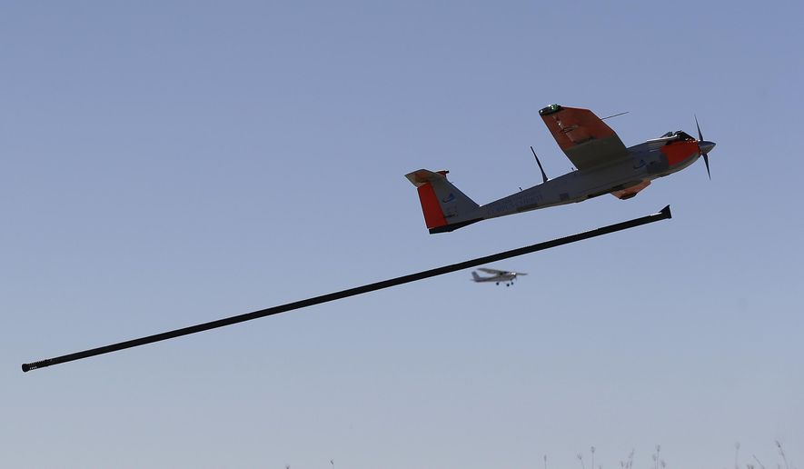 ** FILE ** This Jan. 15, 2014, file photo shows a test drone as it is is launched by catapult as a trail plane follows on a ranch near Sarita, Texas. (AP Photo/Eric Gay, File)