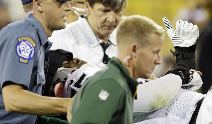Oakland Raiders' Sio Moore gives a thumbs up as he is taken off the field on a stretcher during the first half of an NFL preseason football game against the Green Bay Packers Friday, Aug. 22, 2014, in Green Bay, Wis. (AP Photo/Tom Lynn)
