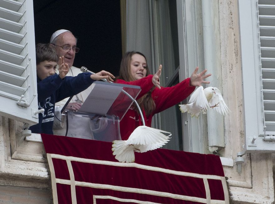 Slavery is one of the themes Pope Francis will discuss in his 2015 World Day of Peace message. Here, he looks at two children as they free doves during his Angelus prayer. (AP Photo/Gregorio Borgia)