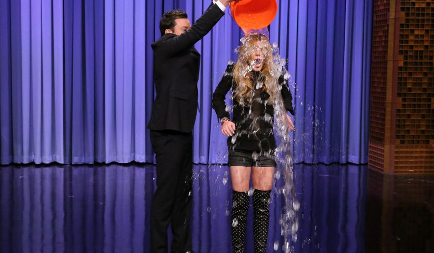 """This Aug. 20, 2014 photo released by NBC shows host Jimmy Fallon, left, dumping a bucket of ice water over the head of actress Lindsay Lohan as she participates in the ALS Ice Bucket Challenge on """"The Tonight Show Starring Jimmy Fallon,"""" in New York. The phenomenal success of the fundraising craze is making charitable organizations rethink how they connect with a younger generation of potential donors, specifically through social media. (AP Photo/NBC, Douglas Gorenstein)"""