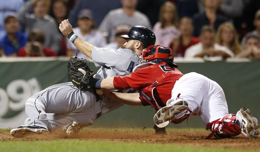 Boston Red Sox's Christian Vazquez, right, puts on a late tag as Seattle Mariners' Dustin Ackley, left, scores on a single hit by Robinson Cano during the ninth inning of a baseball game in Boston, Friday, Aug. 22, 2014. (AP Photo/Michael Dwyer)