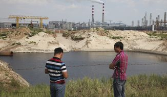 """In this Friday, Aug. 8, 2014 photo, farmer Adiya, right, stands in front of a pond of waste water near a state-of-the-art power plant that turns millions of tons of coal every year into methane in northern China's Inner Mongolia province. As a boy growing up there, Adiya could ride his horse through waist-high grass for miles without meeting another person. Now, the 32-year-old says he stays indoors some mornings because of the industrial stench. Since the plant started running in December, it has obscured the blue skies above Adiya's home with smoke while black pools of wastewater have turned up in the grasslands. """"I only wish they could build this factory in Beijing,"""" said Adiya, who uses only one name, as is Mongolian custom. (AP Photo/Jack Chang)"""