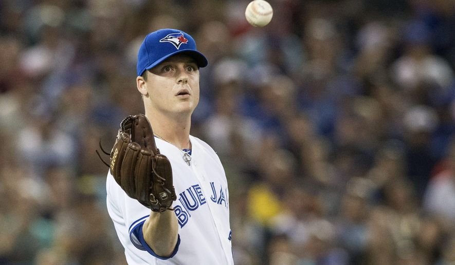 Toronto Blue Jays pitcher Aaron Loup collects the ball as he works against the Tampa Bay Rays during the sixth inning of a baseball game, Friday, Aug. 22, 2014 in Toronto. (AP Photo/The Canadian Press, Chris Young)