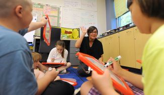 In this 2013 photo parent Amy Rowles helps out at Allen Frear Elementary school in Camden, Del., which won the state's Lt. Governor's award for parental involvement. (AP Photo/The News Journal, Gary Emeigh)