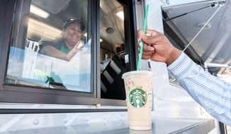 In this photo taken on Thursday, Aug. 1, 2014, Starbucks barista Laura Rodriguez serves up a drink while practicing inside a mobile truck on James Madison University campus in Harrisonburg, Va. The new mobile pilot program is only running in two other universities across the nation. (AP Photo/The Daily News-Record, Nikki Fox)