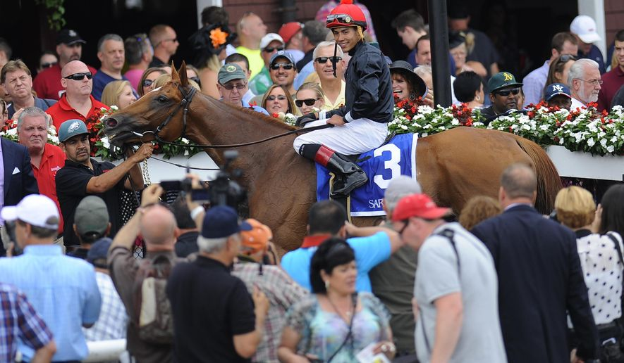 Abaco with jockey Jose Oritz are led in the winners circle after wining the Ballston Spa Stakes horse race at Saratoga Race Course in Saratoga Springs, N.Y., Saturday, Aug. 23, 2014. (AP Photo /Hans Pennink)