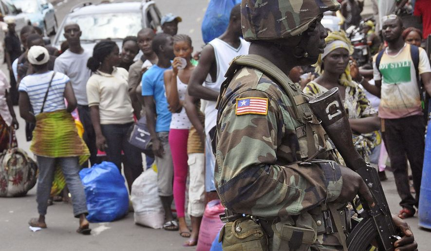 A Liberian soldier, right,  scans people for signs of the Ebola virus, as they control people from entering the West Point area in the city of Monrovia, Liberia, Saturday, Aug. 23, 2014. The outbreak also continues to spread elsewhere in West Africa, with 142 more cases recorded, bringing the new total to more than 2,600 with over 1,400 deaths, the World Health Organization said Friday. Most of the new cases are in Liberia, where the government was delivering donated rice to a slum where 50,000 people have been sealed off from the rest of the capital in an attempt to contain the outbreak. (AP Photo/Abbas Dulleh)