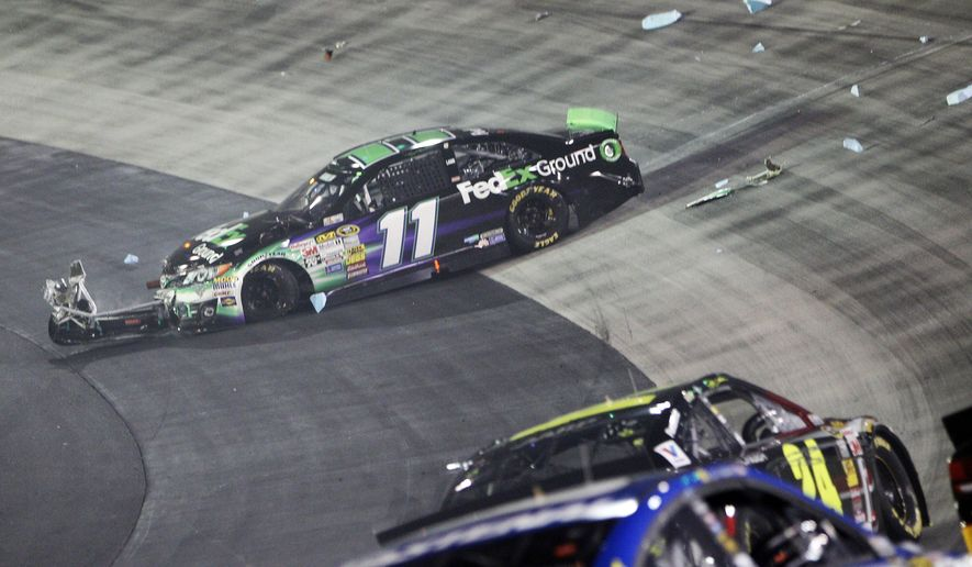 Driver Denny Hamlin (11) sits on the apron after being wrecked by Kevin Harvick during a NASCAR Sprint Cup Series auto race at Bristol Motor Speedway on Saturday, Aug. 23, 2014, in Bristol, Tenn. (AP Photo/Wade Payne)