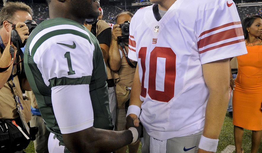 CORRECTS DAY AND DATE - New York Jets quarterback Michael Vick (1) talks with New York Giants quarterback Eli Manning (10) after a preseason NFL football game, Friday, Aug. 22, 2014, in East Rutherford, N.J. The Giants won 35-24. (AP Photo/Bill Kostroun)