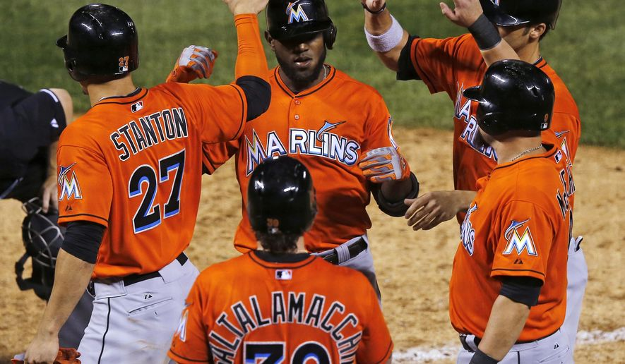 Miami Marlins' Marcell Ozuna is congratulated by teammates Giancarlo Stanton, Jarrod Saltalamacchia, Casey McGehee, right front, and Christian Yelich as he crosses home plate after hitting a grand slam off Colorado Rockies relief pitcher Juan Nicasio during the ninth inning of a baseball game Friday, Aug. 22, 2014, in Denver. (AP Photo/Jack Dempsey)