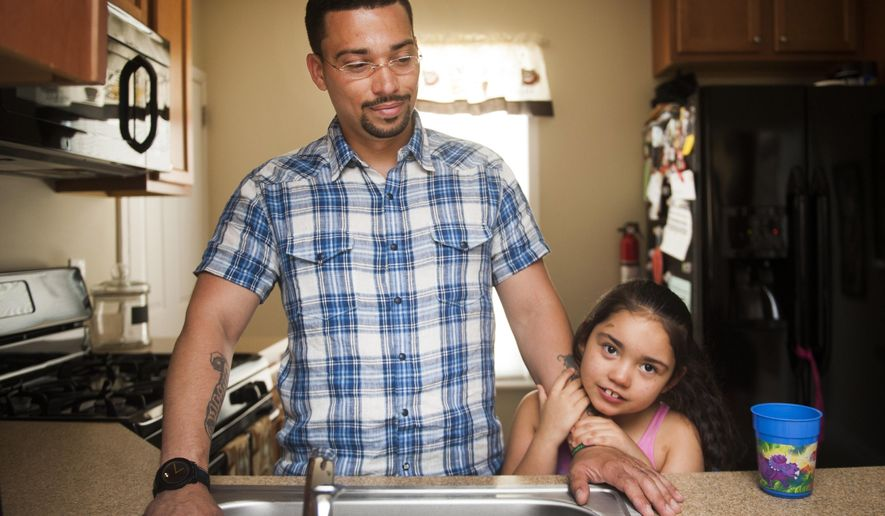 """In this July 31, 2014 photo, Tatyana """"Tuffy"""" Rivera, 7, holds on to her father, Ricardo, in the kitchen of their Camden County, N.J. home. Diagnosed at 10 months with a severe form of epilepsy called Lennox-Gastaut syndrome, Tatyana suffered up to 300 seizures a day, but gets significant relief since her father started treating with marijuana-infused coconut oil he cooks up for her on the stove. (AP Photo/Courier-Post, Jodi Samsel)"""