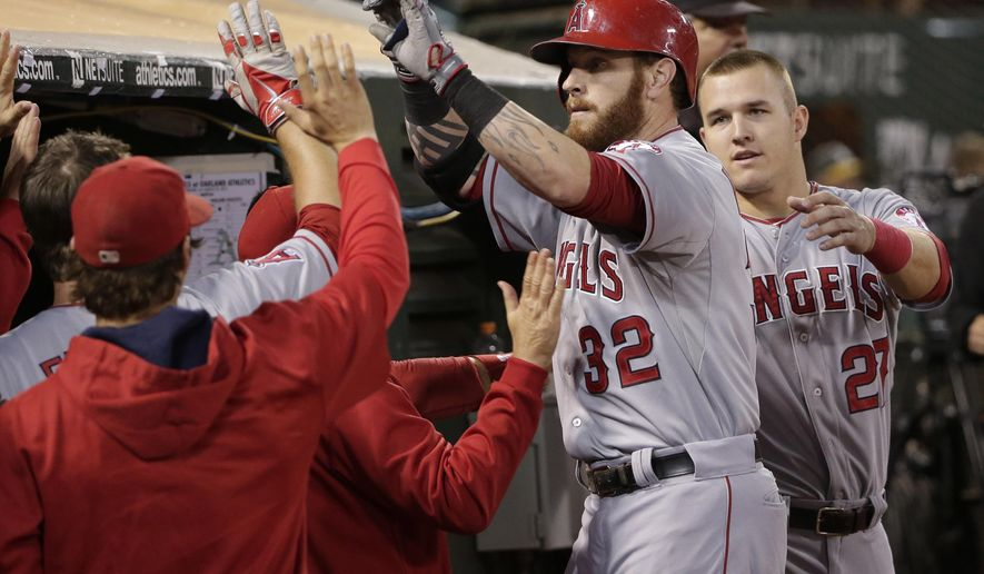 Los Angeles Angels' Josh Hamilton (32) is high-fived in the dugout after his solo home run against the Oakland Athletics during the fourth inning of a baseball game on Friday, Aug. 22, 2014, in Oakland, Calif. (AP Photo/Marcio Jose Sanchez)