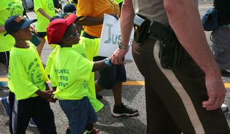 St. Louis County Police Sgt. Colby Dolly joins hands with five-year-old Zion King Frenchie during a march with members of the St. Louis chapters of the NAACP and the National Urban League on West Florissant Avenue in Ferguson, Mo., on Saturday, Aug. 23, 2014. Ferguson's streets remained peaceful as tensions between police and protesters continued to subside after nights of violence and unrest that erupted when Officer Darren Wilson, a white police officer, fatally shot Michael Brown, an unarmed black 18-year-old. (AP Photo/St. Louis Post-Dispatch, Robert Cohen)