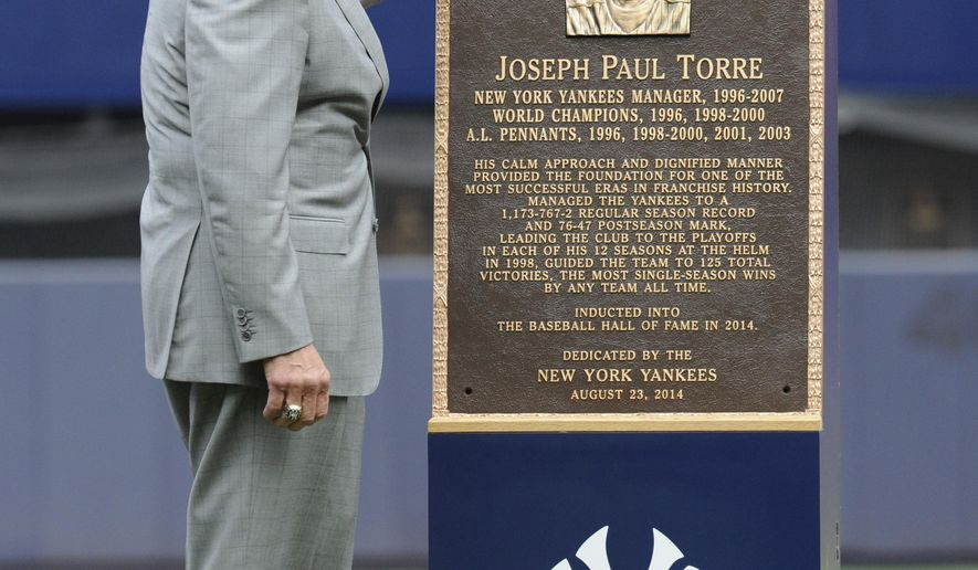 Former New York Yankees manager Joe Torre looks at a replica of his plaque that will hang in Monument Park as the Yankees retired his number before a baseball game against the Chicago White Sox Saturday, Aug. 23, 2014, at Yankee Stadium in New York. (AP Photo/Bill Kostroun)