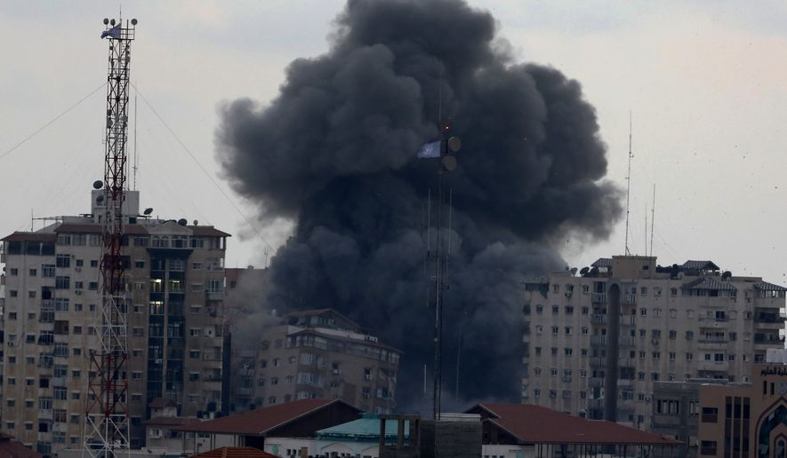 Smoke rises as the al-Zafer apartment tower collapses following an Israeli air strike in Gaza City, in the northern Gaza Strip, Saturday, Aug. 23, 2014. Israeli aircraft fired two missiles at a 12-story apartment tower in downtown Gaza City on Saturday, collapsing the building, sending a huge fireball into the sky and wounding at least 22 people, including 11 children, witnesses and Palestinian officials said. (AP Photo/Adel Hana)