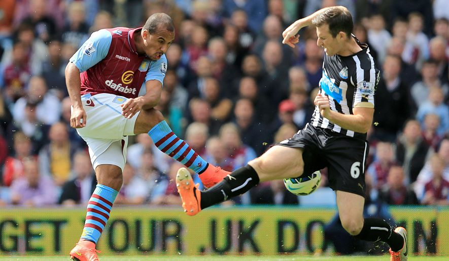 Aston Villa's Gabriel Agbonlahor, left, and Newcastle United's Mike Williamson battle for the ball during the English Premier League match at Villa Park, Birmingham, England, Saturday Aug. 23, 2014. (AP Photo/PA, David Davies) UNITED KINGDOM OUT  NO SALES  NO ARCHIVE