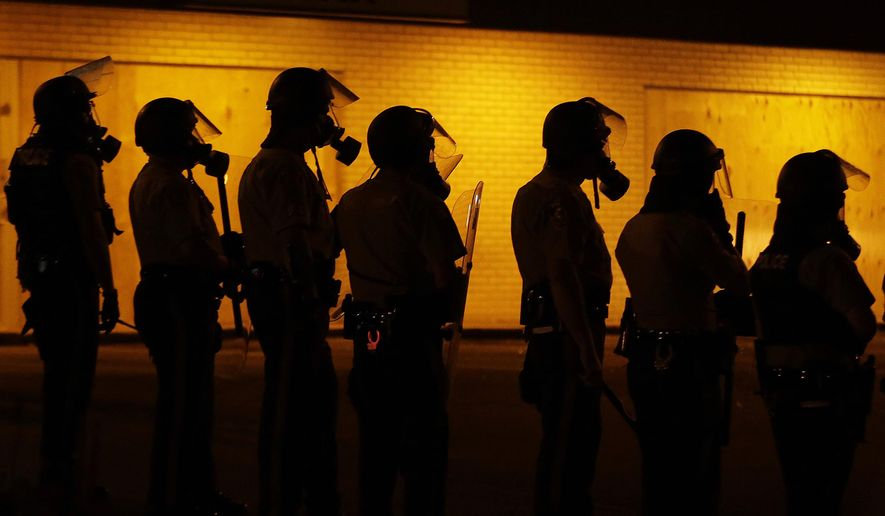 FILE - In this Aug. 17, 2014 file photo, police wait to advance after tear gas was used to disperse a crowd during a protest for Michael Brown, who was killed by a police officer in Ferguson, Mo. Since the shooting, many residents have been afraid to leave their homes at night as protesters clash with police in sometimes violent confrontations. (AP Photo/Charlie Riedel, File)