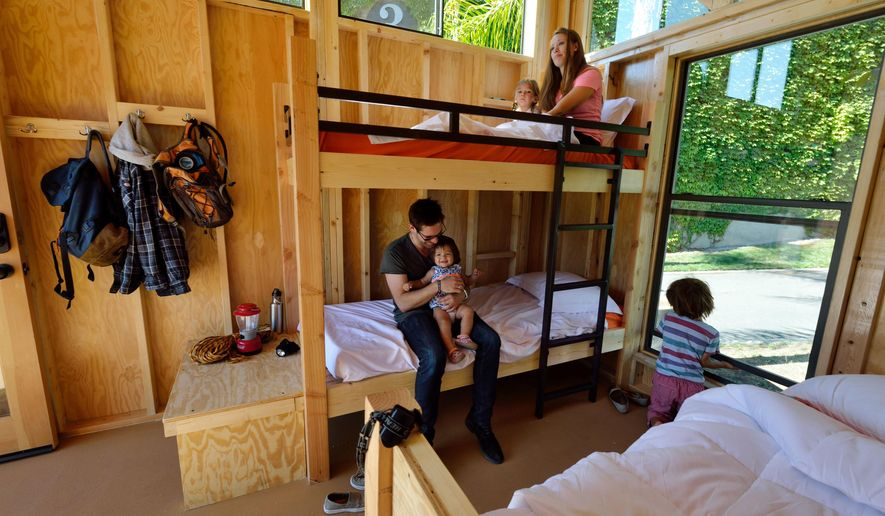 This July 24, 2014 photo released by California State Parks shows Cal Poly Pomona Architecture students Emily Williams, top, and Bryan Charney as they pose for photos with children in a cabin called The Wedge, one of four designs that Parks Forward proposes to put on hundreds of campsites throughout the California State Parks system, displayed at the State Fair Exhibit in Sacramento, Calif. Parks Forward, a group formed by the state to help revamp California's state parks, wants to open up their natural beauty to a wider array of people than typical campers by designing cabins to attract people to the parks who don't typically camp because they don't have expensive equipment, such as tents, or they don't want to sleep outside on the ground. (AP Photo/California State Parks, Brian Baer)