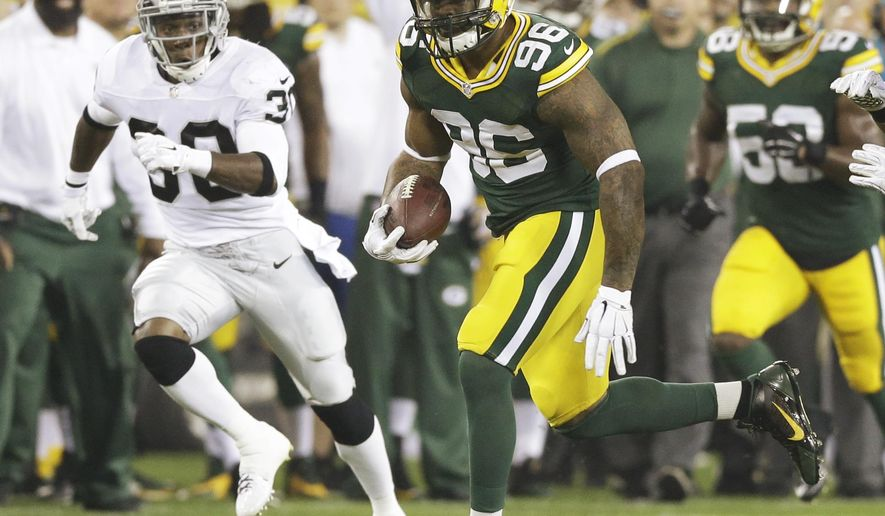 Green Bay Packers' Mike Neal runs with the ball after recovering a fumble during the first half of an NFL preseason football game against the Oakland Raiders Friday, Aug. 22, 2014, in Green Bay, Wis. (AP Photo/Tom Lynn)