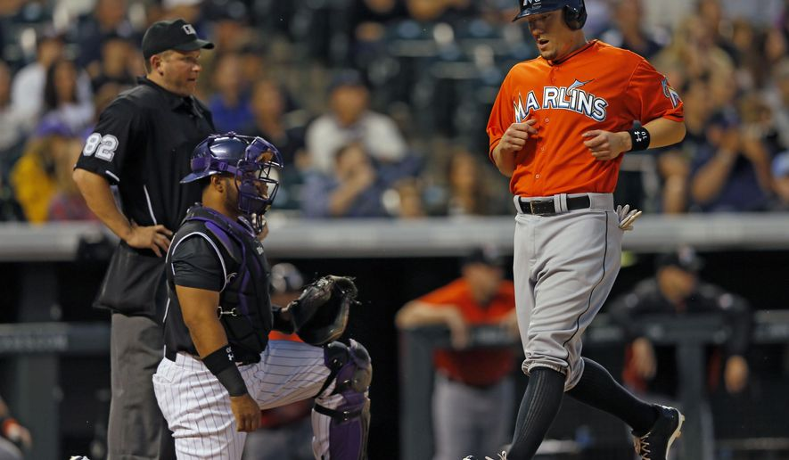 Colorado Rockies catcher Wilin Rosario looks on as Miami Marlins' Jeff Baker scores on a Giancarlo Stanton RBI double during the third inning of a baseball game Friday, Aug. 22, 2014, in Denver. (AP Photo/Jack Dempsey)