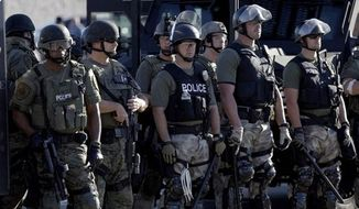 ** FILE ** Police watch protesters in Ferguson, Mo. on Wednesday, Aug. 13, 2014. (Associated Press)
