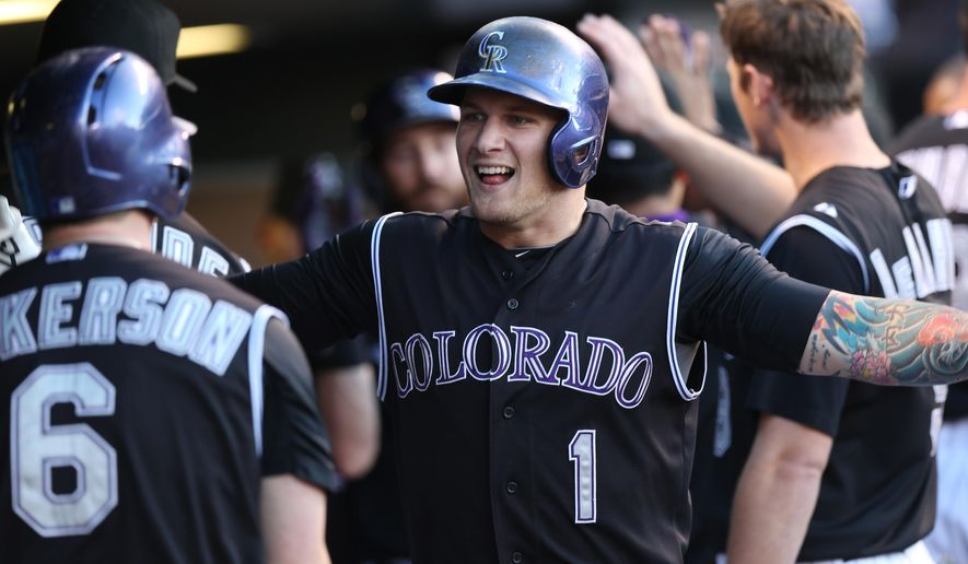 Colorado Rockies' Corey Dickerson, left, congratulates Brandon Barnes after his two-run home run against the Miami Marlins in the third inning of a baseball game in Denver on Saturday, Aug. 23, 2014. (AP Photo/David Zalubowski)