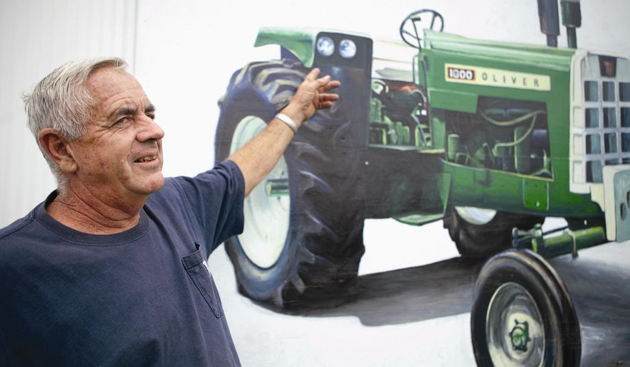 ADVANCED FOR RELEASE SUNDAY, AUGUST 24, 2014 Jack May points out some details that artist Zack Jones put into a painting of an 1800 Oliver Diesel tractor on the side of May's outbuilding, Aug. 21, 2014. (AP Photo/The Daily Nonpareil, Joe Shearer)