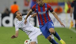 Ludogorets Razgrad's Marcelinho, left, falls after a tackle by Steaua Bucharest's Cornel Rapa, right, during the first leg of a Champions League playoff soccer match at the National Arena stadium in Bucharest, Romania, Tuesday, Aug. 19, 2014.(AP Photo/Vadim Ghirda)