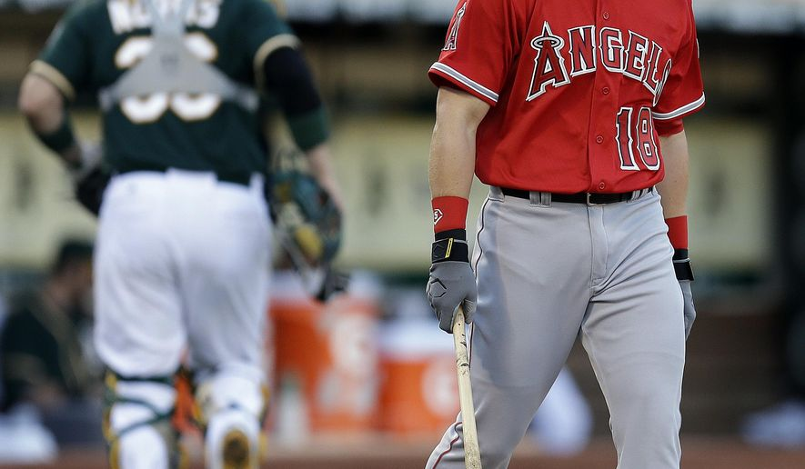 Los Angeles Angels' Gordon Beckham, right, blows a bubble after being called out on strikes from Oakland Athletics' Jon Lester in the second inning of a baseball game Saturday, Aug. 23, 2014, in Oakland, Calif. (AP Photo/Ben Margot)