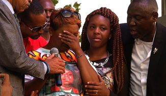 Lesley McSpadden, Michael Brown's mother, second from left, covers her eyes at Peace Fest, Sunday, Aug. 24, 2014, in St. Louis. Hundreds of people gathered in St. Louis' largest city park Sunday at a festival that promoted peace over violence. (AP Photo/Alex Sanz)