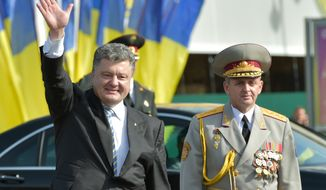 Ukrainian President Petro Poroshenko, left, waves to people in Kiev, Ukraine, Sunday, Aug. 24, 2014. Ukraine's president announced plans Sunday to boost his country's defense spending by an estimated 50 percent as government forces seek to overpower pro-Russian separatists in the east. President Petro Poroshenko made his pledge to spend an extra 40 billion hryvnia ($3 billion) by 2017 during a speech marking Ukraine's independence from the Soviet Union in 1991. (AP Photo/Presidential Press Service, Mykhailo Markiv, Pool)