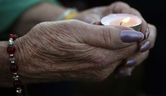A woman holds a candle during a vigil for James Foley in his hometown of Rochester, New Hampshire Saturday. Several hundred people attended and paid tribute to the freelance American journalist who was killed earlier in the week by Islamic State militants. (AP Photo/Jim Cole)