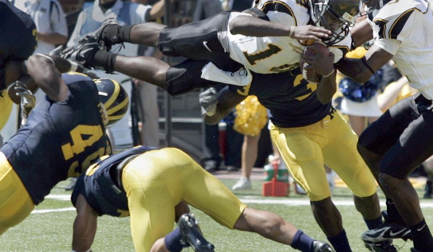 **FILE** In this Sept. 1, 2007 file photo, Appalachian State quarterback Armanti Edwards dives over Michigan linebacker John Thompson (49) and cornerback Brandon Harrison to score their fourth touchdown of the game during the second quarter of a college football game in Ann Arbor, Mich. Michigan is opening its 2014 season with Appalachian State this week, rekindling flashbacks to the day the Wolverines were on the wrong end of one of the biggest upsets in college football history.   (AP Photo/Duane Burleson, File)