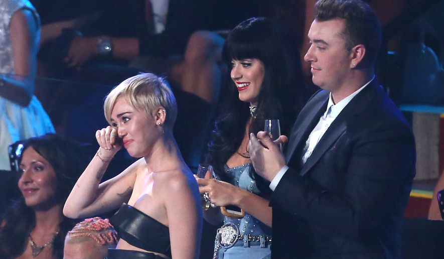 Miley Cyrus, left, accepts the award for Video of the Year at the MTV Video Music Awards at The Forum on Sunday, Aug. 24, 2014, in Inglewood, Calif. (Photo by Matt Sayles/Invision/AP)