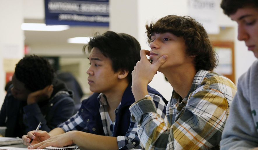 FILE - In this Feb. 7, 2014 file photo, students Julian Lopez, second left, Ben Montalbano, second right and James Agostino, right, listen during their Advanced Placement (AP) Physics class at Woodrow Wilson High School in Washington. A new policy from the American Academy of Pediatrics recommends delaying classes for all teens until at least 8:30 a.m. to curb their widespread lack of sleep, which has been linked with poor health, bad grades, car crashes and other problems. The policy was published online Monday, Aug. 25, 2014, in Pediatrics. (AP Photo/Charles Dharapak, File)