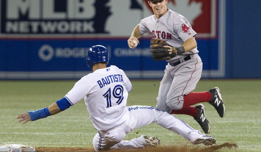Boston Red Sox's Brock Holt gets the force out on Toronto Blue Jays' Jose Bautista at second base but fails to turn the double play on a ground ball hit by Adam Lind during the ninth inning of a baseball game Monday, Aug. 25, 2014, in Toronto. (AP Photo/The Canadian Press, Fred Thornhill)