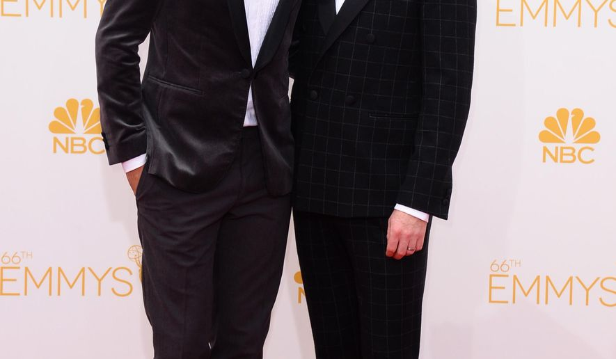 Justin Mikita, left, and Jesse Tyler Ferguson arrive at the 66th Annual Primetime Emmy Awards at the Nokia Theatre L.A. Live on Monday, Aug. 25, 2014, in Los Angeles. (Photo by Jordan Strauss/Invision/AP)